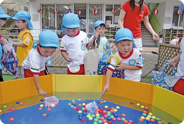 夏祭りで水の中のボールを取ろうとしている子どもたち