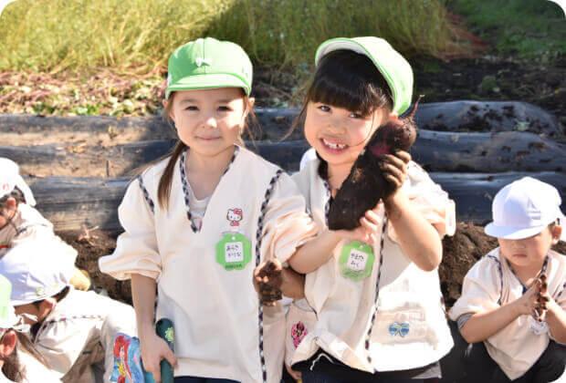 お芋掘りで掘った芋を持つ子どもたち