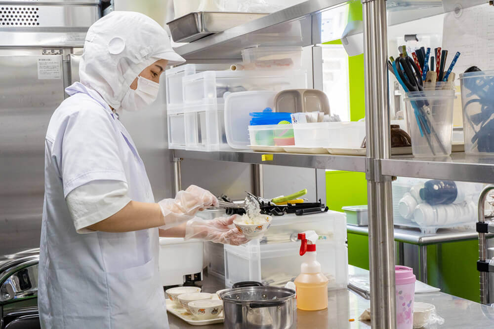 清潔なキッチンでご飯の盛り付けをする女性